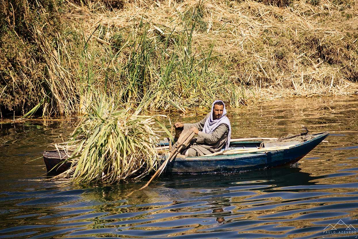 pescador num barco cheio de juncos no nilo